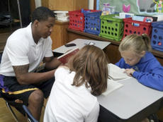 """<div class=""""source"""">Photo submitted</div><div class=""""image-desc"""">St. Catharine men's basketball assistant coach Brandon Johnson read a novel with two students during their Language Arts class. Patriot Pals will be spending 30 minutes each Friday with the class.</div><div class=""""buy-pic""""></div>"""