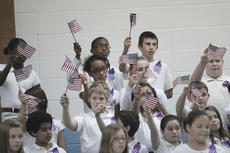 "<div class=""source"">Photo by John Overby</div><div class=""image-desc"">Above, students showed their patriotic spirit during one of the songs to honor troops last week.</div><div class=""buy-pic""><a href=""/photo_select/15336"">Buy this photo</a></div>"