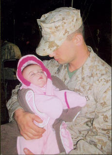 """<div class=""""source"""">Parrish Family Photo</div><div class=""""image-desc"""">Washington County native and United States Marine Zack Parrish held his young daughter, Lily Jo, just hours before being deployed to Afghanistan on Dec. 21, 2009. Parrish will get to be home for the holidays this year before being deployed again in the summer of 2011.</div><div class=""""buy-pic""""></div>"""