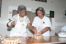 "<div class=""source"">Jeff Moreland</div><div class=""image-desc"">DeLoise Logan and Pam Grundy were busy preparing cakes Thursday for this weekend's homecoming celebration at Holy Rosary Catholic Church.</div><div class=""buy-pic""><a href=""/photo_select/1208"">Buy this photo</a></div>"