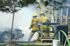 """<div class=""""source"""">Photo by Brandon Mattingly</div><div class=""""image-desc"""">Washington County firefighters work to put out a car fire.</div><div class=""""buy-pic""""><a href=""""/photo_select/14108"""">Buy this photo</a></div>"""