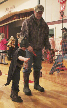 """<div class=""""source"""">Photo by Brandon Mattingly</div><div class=""""image-desc"""">Eastwood Settles, 4, son of Joey and Marsha Settles, takes a crack at a ring-tossing game at the Mackville Community Center on Thursday.</div><div class=""""buy-pic""""><a href=""""http://web2.lcni5.com/cgi-bin/c2newbuyphoto.cgi?pub=023&orig=img_2685-1.jpg"""" target=""""_new"""">Buy this photo</a></div>"""