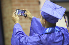 """<div class=""""source"""">Photo by John Overby</div><div class=""""image-desc"""">Christian Ibarra takes a selfie on his way to walk across the stage at Friday's ceremony.</div><div class=""""buy-pic""""><a href=""""/photo_select/16510"""">Buy this photo</a></div>"""