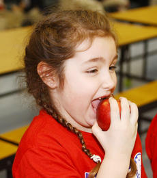"""<div class=""""source"""">Jeff Moreland</div><div class=""""image-desc"""">Ella Flugan, a first grader at Washington County Elementary School, enjoyed a healthy snack as she ate the apple that came with her lunch Friday.</div><div class=""""buy-pic""""><a href=""""/photo_select/7984"""">Buy this photo</a></div>"""