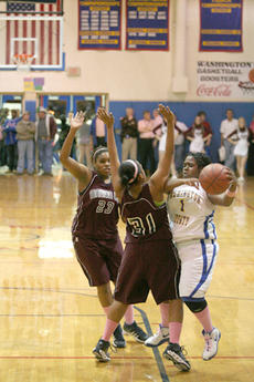 "<div class=""source"">Jimmie Earls</div><div class=""image-desc"">Pooh Railey battles against Marion County defenders Shakila Goodin (31) and Alyson King (23) during Friday night's matchup between the Commanderettes and the Lady Knights. Marion County came away with the 68-42 win over Washington County.</div><div class=""buy-pic""><a href=""/photo_select/337"">Buy this photo</a></div>"