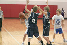 """<div class=""""source"""">Jimmie Earls</div><div class=""""image-desc"""">Anthony Osbourne, left, tries to find a way around two Elizabethtown defenders in middle school hardwood action on Saturday afternoon.</div><div class=""""buy-pic""""><a href=""""/photo_select/6017"""">Buy this photo</a></div>"""