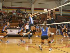 "<div class=""source"">Jimmie Earls</div><div class=""image-desc"">Washington County senior middle hitter Clare Smith, center, gets some major air as she comes up with a big block against the E-Town attack in volleyball action last Tuesday.</div><div class=""buy-pic""><a href=""/photo_select/3398"">Buy this photo</a></div>"