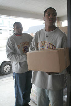 """<div class=""""source"""">Jimmie Earls</div><div class=""""image-desc"""">Senior forward Kevin Owens, left, and sophomore guard Brandon Johnson, right, work as part of an assembly line to get items out of the cold.</div><div class=""""buy-pic""""><a href=""""/photo_select/6179"""">Buy this photo</a></div>"""