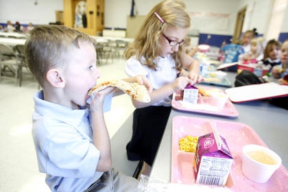 Dustin Taylor, left, munched on pizza, while Emma Mattingly, right, opened her milk at lunch.