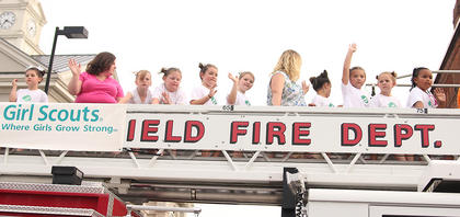 A group of local Girl Scouts waved to the crowd as they enjoyed a ride atop a fire truck during Friday evenings parade.