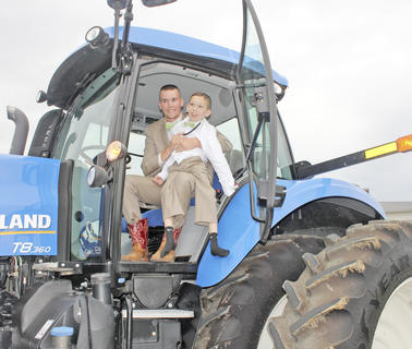 Shawn Byrd helps his brother, Darrol, 12, down from the New Holland tractor that Shawn drove to prom.