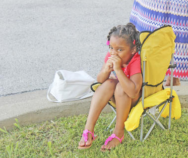 Salaizah Sheckles, 4, enjoys a snack while she takes in all of the festivities during the event.