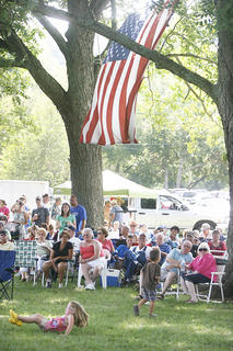 A large American flag hung from the trees by the stage.