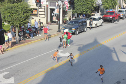 Youngsters chase each other across Main Street as the Snappy Tomato greets festival-goers.