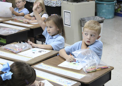 Caroline Smith raises her hand in Deanna McElroy's kindergarten class at St. Dominic. At right is kindergartener Thomas Roution.