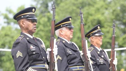 Members of the Marion County Honor Guard salute with their rifles in hand.
