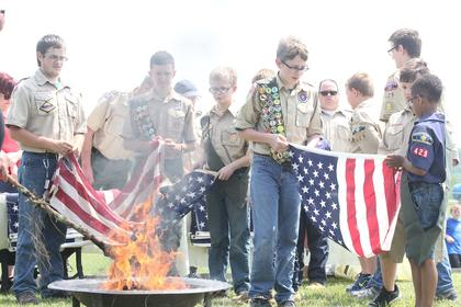 Scouts participate in a flag retiremenet ceremony.
