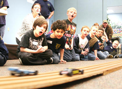 Members of Springfield's Cub Scout Pack 429 participated in the annual Pinewood Derby at the River of Life Church. Scouts watched as two cars zoomed by on the wooden track.