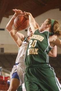 Junior Shay Yocum got sandwiched between Owensboro Catholic sophomore Rebecca Greenwell, back, and junior Stephanie Dooper (20), on the way to the basket.