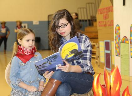 Julianne Simpson enjoys a story read by Emily Simpson.