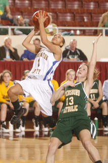 Junior Shay Yocum went to the hoop over Owensboro Catholic sophomore Leah Greathouse in the first half of the Commanderettes&#039; loss. 