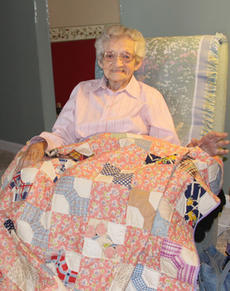 """<div class=""""source"""">Geoff Hamill</div><div class=""""image-desc"""">Clara Mae Blandford at her Kelly Corner home on June 26. Blandford holds a quilt made with a top that could be more than 100 years old. The pink squares in the quilt are from feedsack cloth. </div><div class=""""buy-pic""""><a href=""""/photo_select/14549"""">Buy this photo</a></div>"""