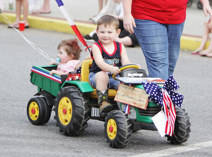 Ethan Reid, 3, drove his little John Deere tractor in the parade, giving his baby sister, Brianna, a ride in the wagon behind him.