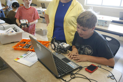 Ethan Osborne received instruction from Katrina Ballard while programming his robot during camp on Friday.