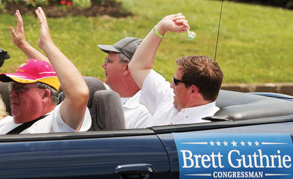 U.S. Rep. Brett Guthrie tosses candy to parade watchers.