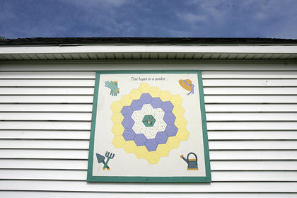 "This barn quilt, titled ""Grandmother's Flower Garden,"" sits at 2242 Bardstown Road. Martha Ann Hardin is the owner. She said it was one of the first quilts in the area."
