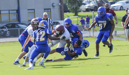 Washington County's Caleb Foster loses his helmet as he drags down a Harrison County runner during the team's scrimmage.