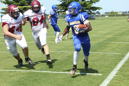 Jatavian Churchill gets by two Harrison County defenders on the sideline during a scrimmage last Saturday morning.