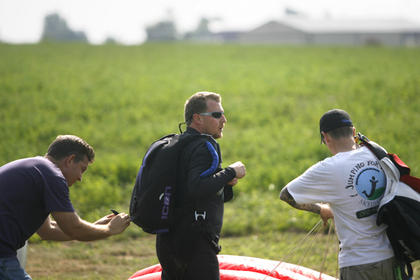 Bobby Trausue, right, and Pete Harris, left, helped Woods with a new parachute immediately after landing.