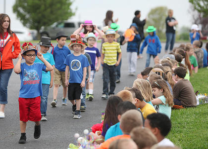 North Washington first grarder Jarrett Arenas holds onto his Derby hat as he and his classmates take part in the school's Derby parade.