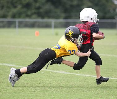 Nash Yates dives to make a touchdown-saving tackle for Washington County Gold in youth football action Saturday against Taylor County.