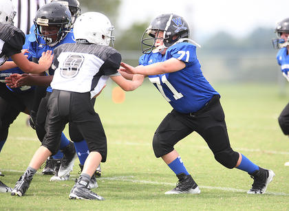 Seth Smith of the Washington County Blue team blocks a Taylor County opponent during youth football action.