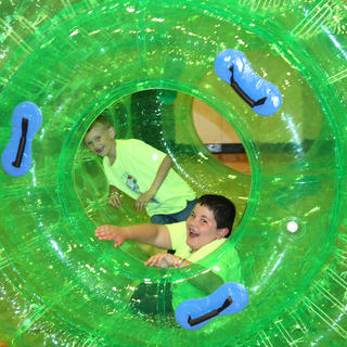 Luke Essex, front, and Gage Campbell have fun rolling around in an inflatable tube.