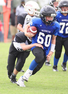 Brady Brown runs the ball for Washington County Blue in youth football action against Taylor County Saturday.