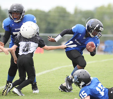 JaKiston Thompson runs the ball for Washington County Blue with some blocking help from DeShyrian Thompson during youth football action Saturday.