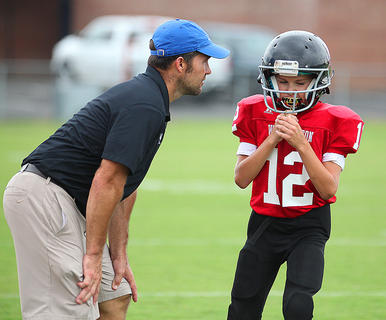 Washington County Red coach Bobby Joe Mattingly talks with his son, quarterback Isaiah Mattingly, during action Saturday.