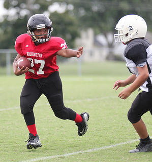 Washington County Red running back Ky'Mani Reardon runs the ball during youth league football action.