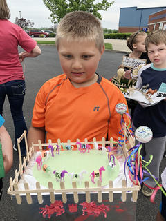 North Washington Elementary Jeremiah Milburn displays his float for the school's annual Kentucky Derby celebration as classmate Brayden Hardin looks on.