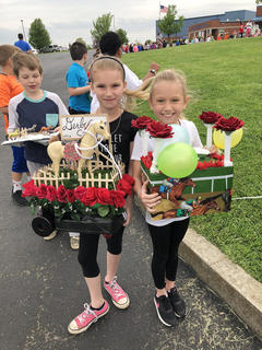 North Washington Elementary second graders Layla Crowe, left, and Claire Mattingly are all smiles as they show off their floats during the school's annual Derby celebration.
