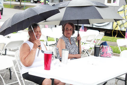 Josie Spaulding, left, and Mary Jean Smith try to stay dry.