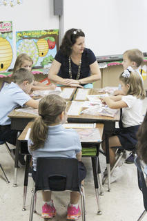 Barbara Lynch, instructional assistant, sits with a group of students at St. Dominic.