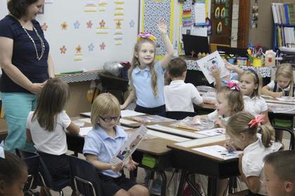 St. Dominic kindergartener Mary Kate Curtsinger raises her hand during class on Thursday morning.