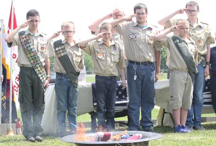 Boy Scouts salute as the flags they prepared for retirement burn during Memorial Day ceremonies.