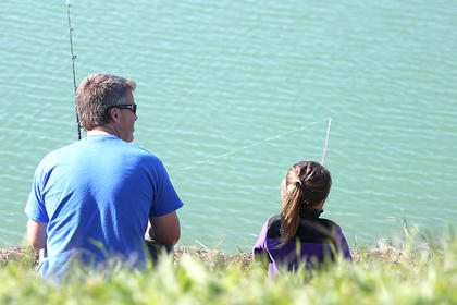 Above, Rowan Cecil, 4, and Scott Cecil wait for the fish to bite at the Jakes Day celebration at River of Life Church on Saturday.