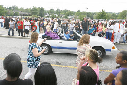 Haylee Kimes (in white car) waved to spectators watching prom-goers enter the Washington County High School prom on Saturday.