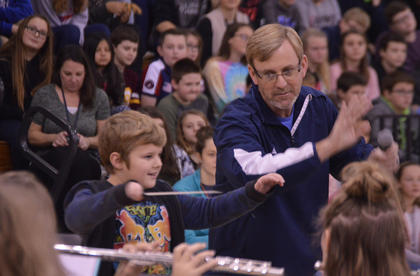 Washington County High School band director Scotty Burns leads the high school band, with some help from guest conductor Jakob Midgett, 9, during the North Washington School's Christmas Band Concert on Thursday, Dec. 13.